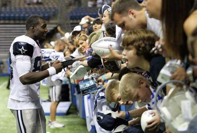 Receiver Dez Bryant (left) signs autographs for fans at the conclusion of the afternoon session of the Dallas Cowboys training camp at the Alamodome on Saturday, July 30, 2011. Kin Man Hui/kmhui@express-news.net Photo: KIN MAN HUI, : / SAN ANTONIO EXPRESS-NEWS