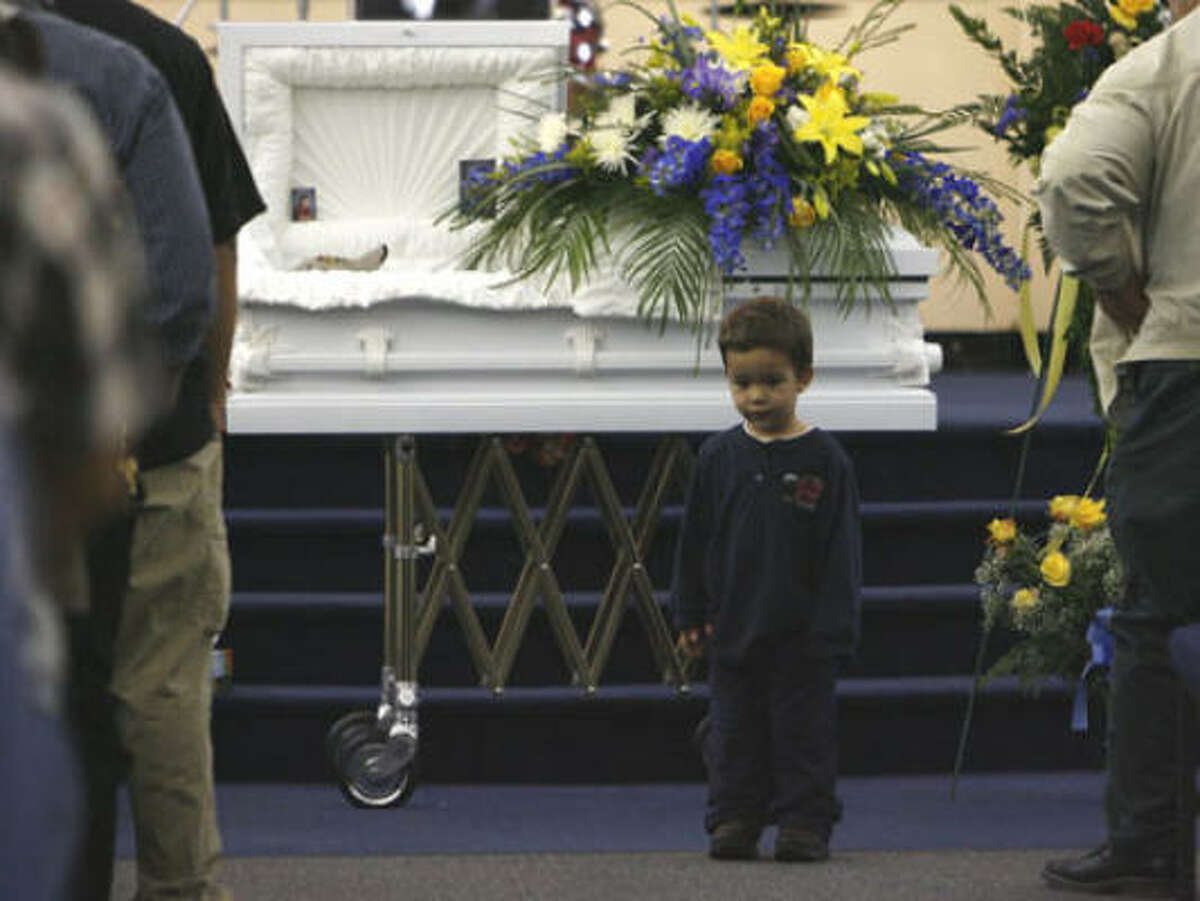 Peter Rios, 2, stands near his older brother during a memorial service Friday for Pedro Rios at the Bethel Christian Center in Pasadena. The 4-year-old died Tuesday after being mauled by two pit bulls outside his home. Peter escaped the attack.