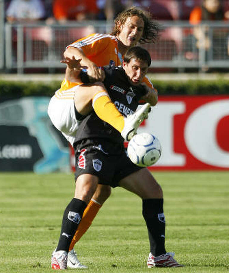 Kelly Gray, left, gets wrapped up with Pachuca's Christian Gimenez during the Dynamo's 2-0 victory Thursday night at Robertson Stadium Photo: Bob Levey, For The Chronicle