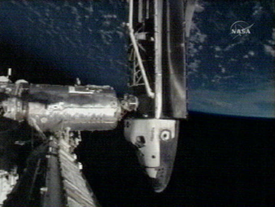 In this image made from video provided by NASA, the Space Shuttle Atlantis is seen docked with the international space station in orbit, with the Earth seen above. Photo: NASA, AP