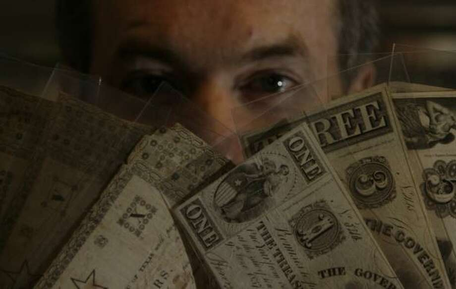 James Bevill, president of the Texas Numismatic Association, displays several of the rare bills that circulated in Texas in the 1800s. The bills are in Bevill's personal collection, and will be on display Friday through Sunday at the association's Houston exhibit. Photo: JULIO CORTEZ, CHRONICLE