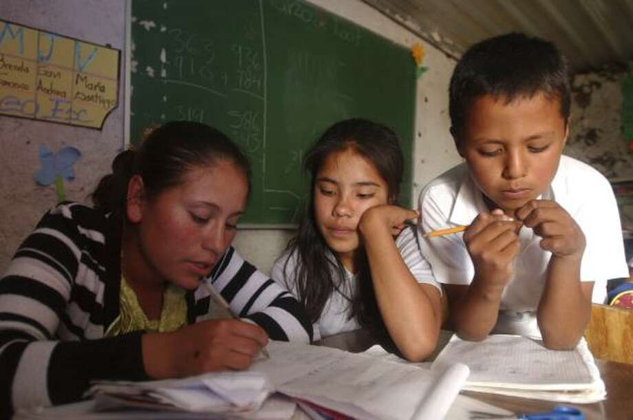 Maria del Pueblito Avila, a student teacher with a high school diploma, corrects her students' work in a one-room schoolhouse in a rural village in the Mexican state of Queretaro. Photo: JENNIFER SZYMASZEK PHOTOS, FOR THE CHRONICLE