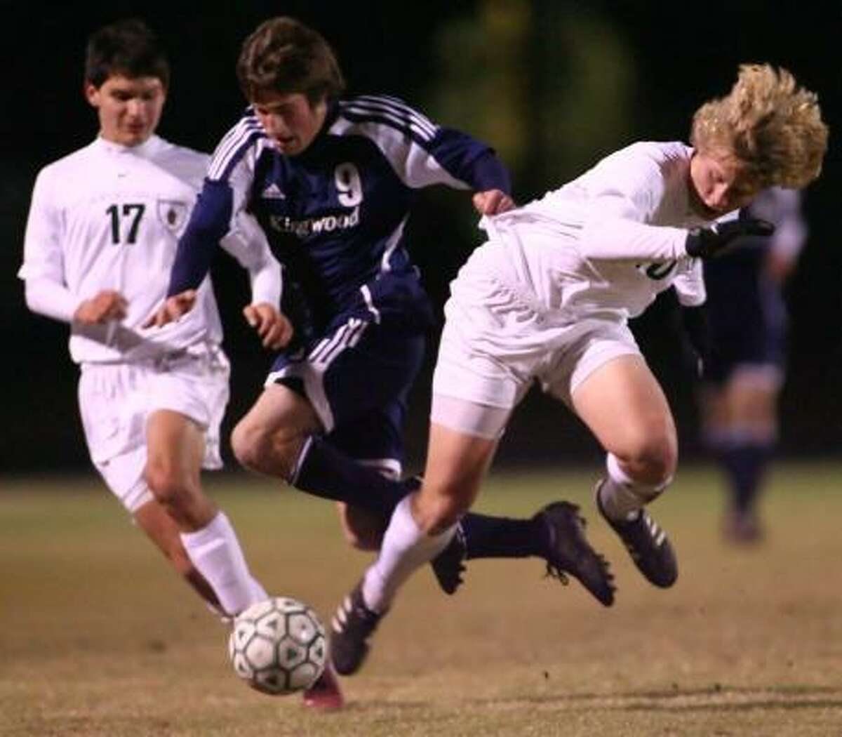 Kingwood's Vinnie Martinelli (9) tries to get past The Woodlands' Conner Mowery (right) and Andrew Norman during their match Friday night at The Woodlands High School.