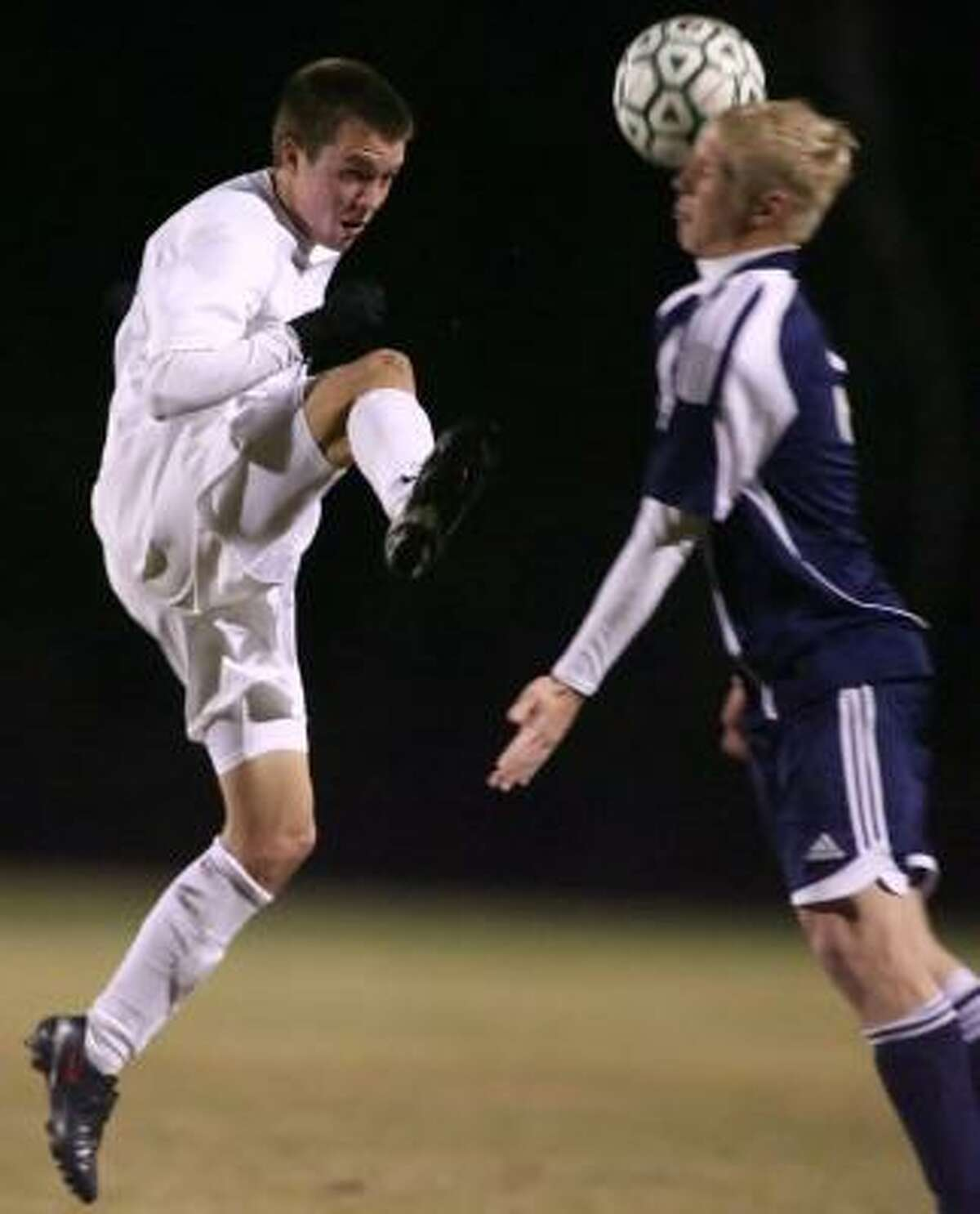 Kingwood's Michael Micheletti (right) takes a kick off his head from The Woodlands' Jordan Phillips during their match Friday night at The Woodlands High School.
