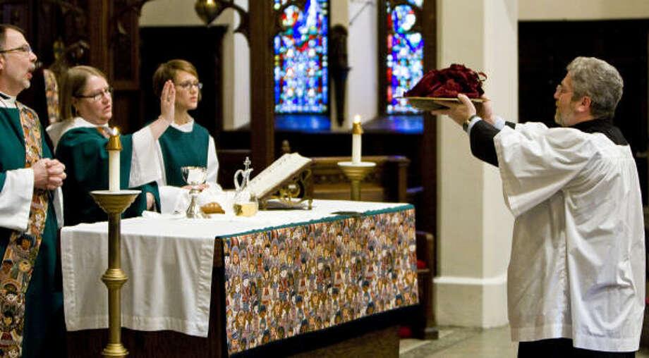 John Washbush, right, presents the collection to deacon Terry Garner, from left, the Rev. Debra Trakel, and Dorota Pruski at St. James Episcopal Church in Milwaukee, Wis. Church offerings have been hit by a tough economy. Photo: TOM LYNN, MCT
