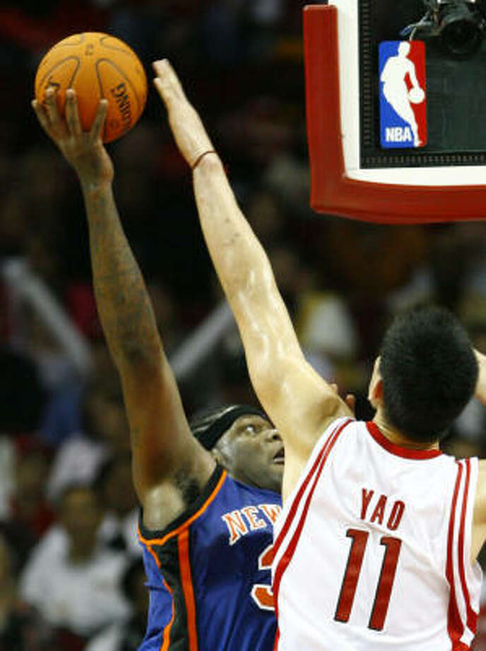Yao Ming also had seven blocked shots, including this one of Eddy Curry in the second quarter. Photo: Nick De La Torre, CHRONICLE