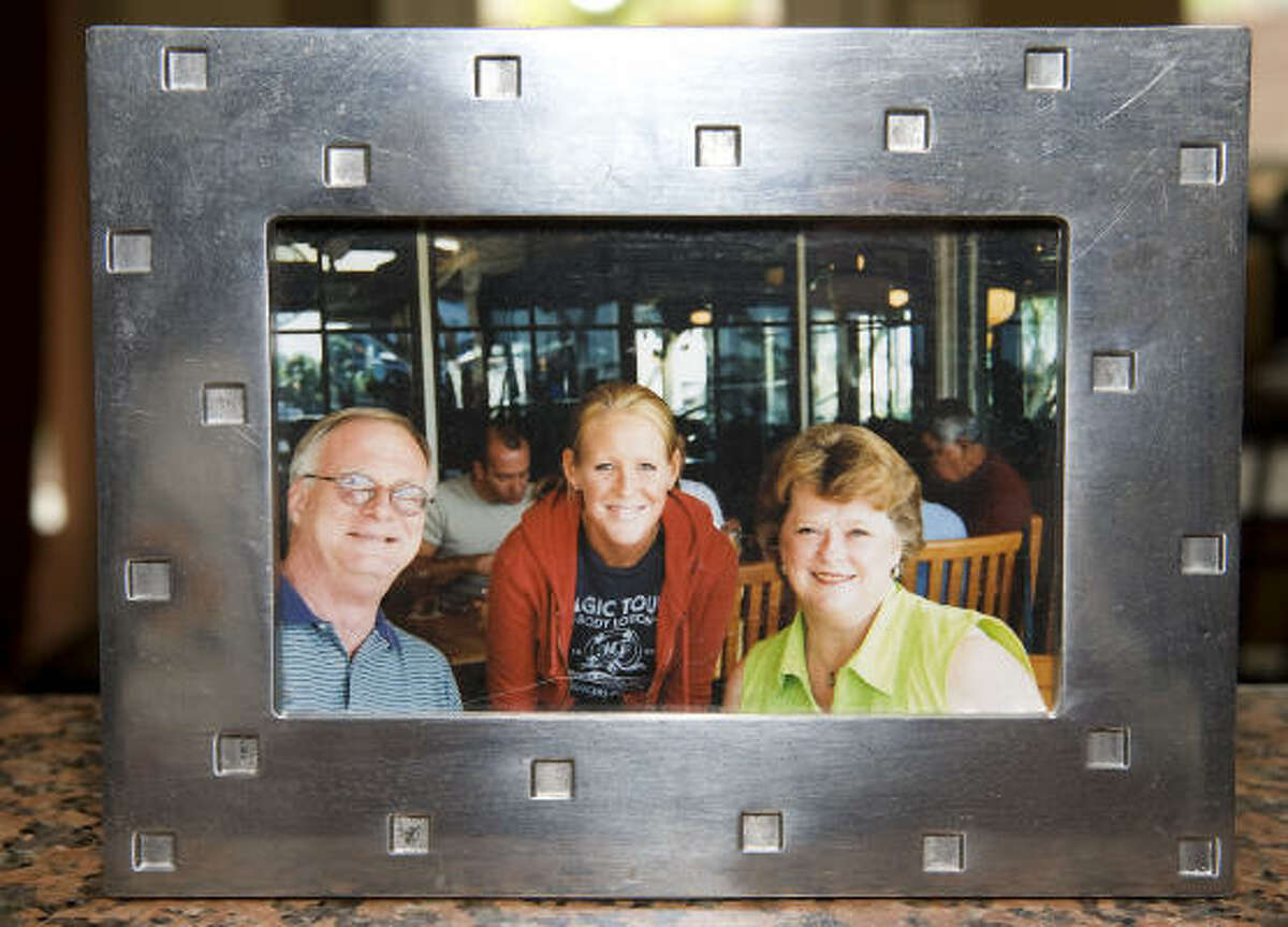 Laura MacRory, center, is shown with her adopted parents, Jimmy and Sharon Gentry.