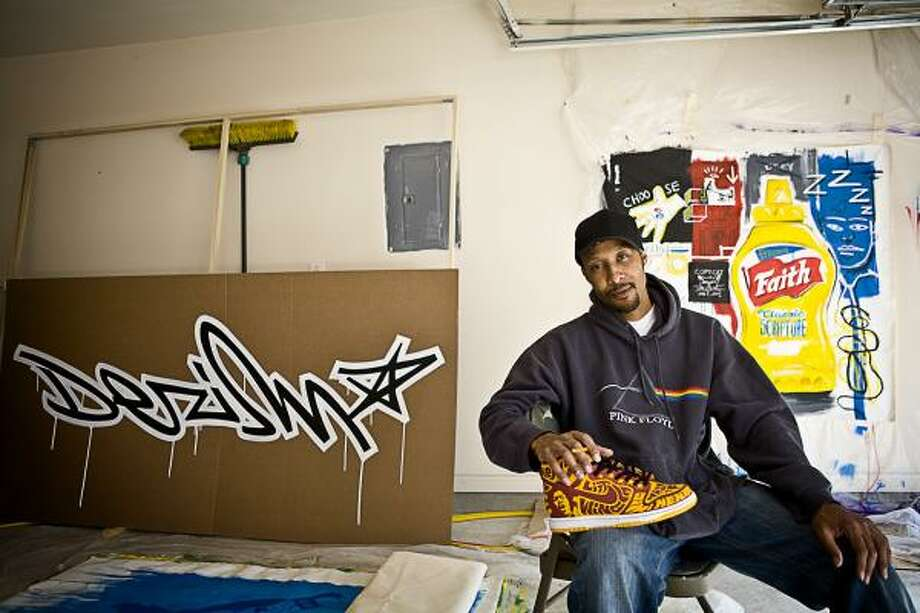 """Desmond """"Dez"""" Woods, a local artist known for his graffiti, airbrushing and sneaker customization and winner of the Mountain Dew Green Label Art contest, works on projects in his home garage, west of Houston. Photo: ERIN TRIEB, FOR THE CHRONICLE"""