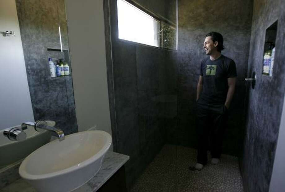 Matt Ford, stands in the concrete shower in his green home in the Heights. Ford is building green houses in Houston including recycled floors, radiant barrier house wraps and a sun-flow system on the roof powered by a solar panel. Photo: Karen Warren, Chronicle