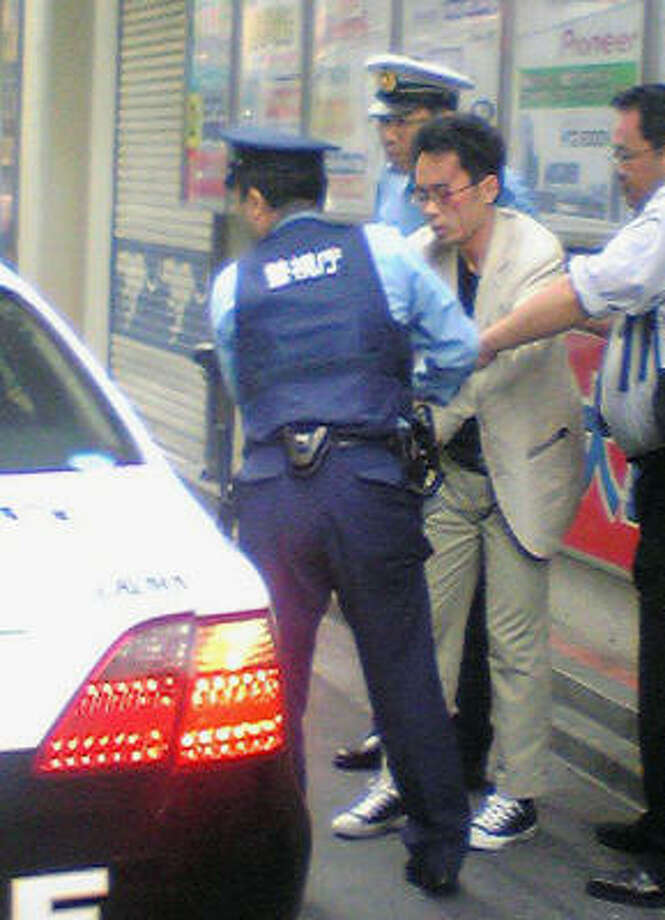 In this image taken by an anonymous pedestrian via Kyodo News, Tomohiro Kato, wearing glasses, is detained by police officers in Tokyo's Akihabara district Sunday, June 8, 2008. The 25-year-old man rammed a truck into a crowd of shoppers, jumped out and went on a stabbing spree in Tokyo's top electronics district Sunday, killing at least seven people and wounding 10 others. Photo: AP