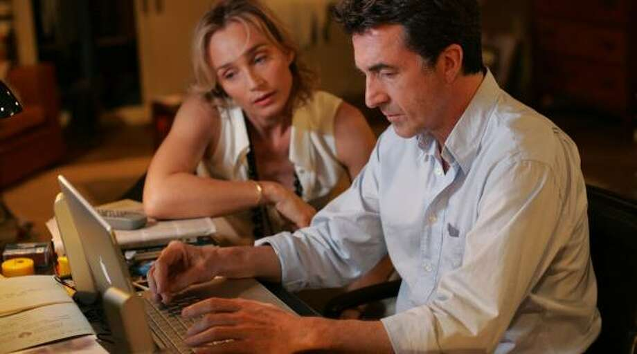 Alex Beck (Francois Cluzet) and friend Helene (Kristin Scott Thomas) check e-mails on his laptop computer in Tell No One. Photo: MUSIC BOX PICTURES