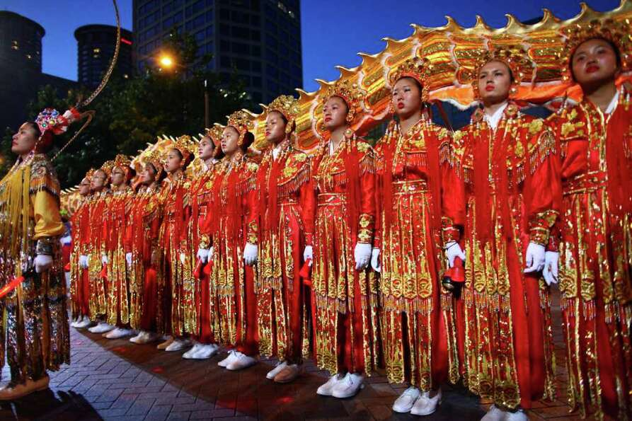 Members of the Seattle Chinese Community Girl's Drill Team perform during the Seafair Torchlight  Pa