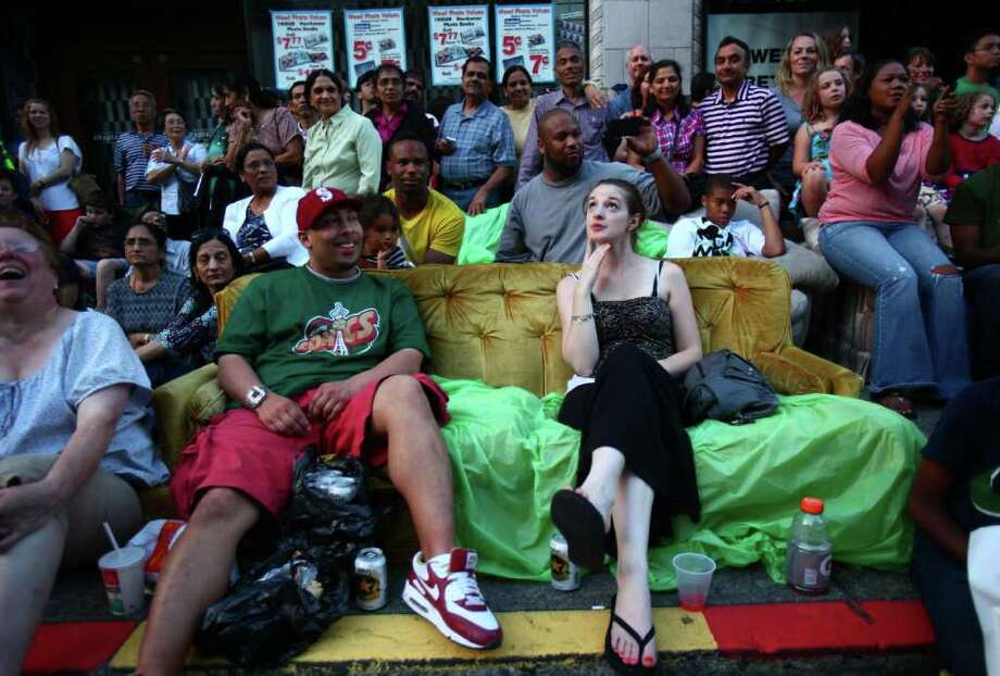 Gaylon Henry, left, and Whitney Johnson watch the parade from the comfort of a couch. Photo: JOSHUA TRUJILLO / SEATTLEPI.COM