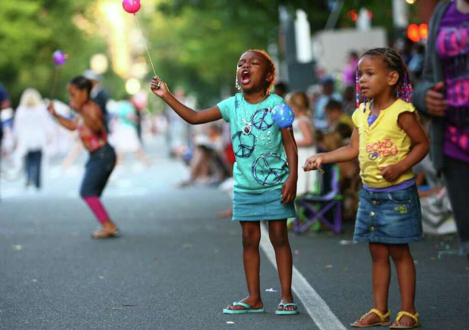 Madison Hunter, 5, in blue, and Amaiyah Metcalf, 4, in yelllow, cheer during the Seafair Torchlight  Parade. Photo: JOSHUA TRUJILLO / SEATTLEPI.COM