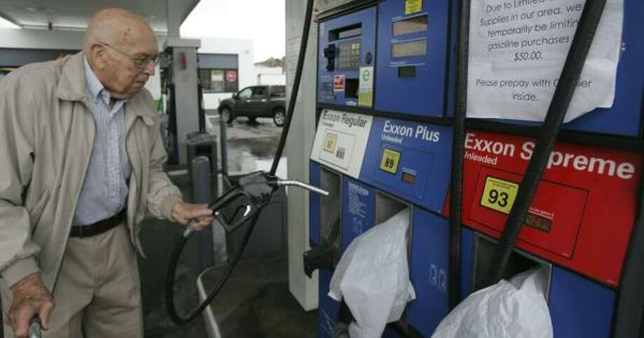 Olin Pugh tries to pump gas at an Exxon station Friday in Columbia, S.C. A sign on the pump asked a limit of $50 per purchase on regular, while medium and premium grades were unavailable. Photo: MARY ANN CHASTAIN, ASSOCIATED PRESS