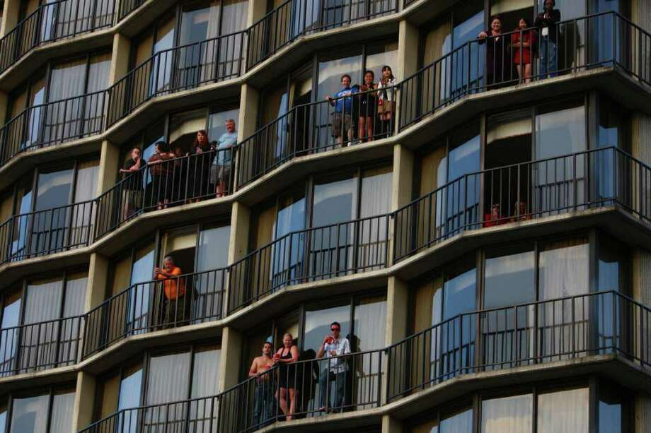 People watch from the Warwick Hotel during the Seafair Torchlight  Parade. Photo: JOSHUA TRUJILLO / SEATTLEPI.COM