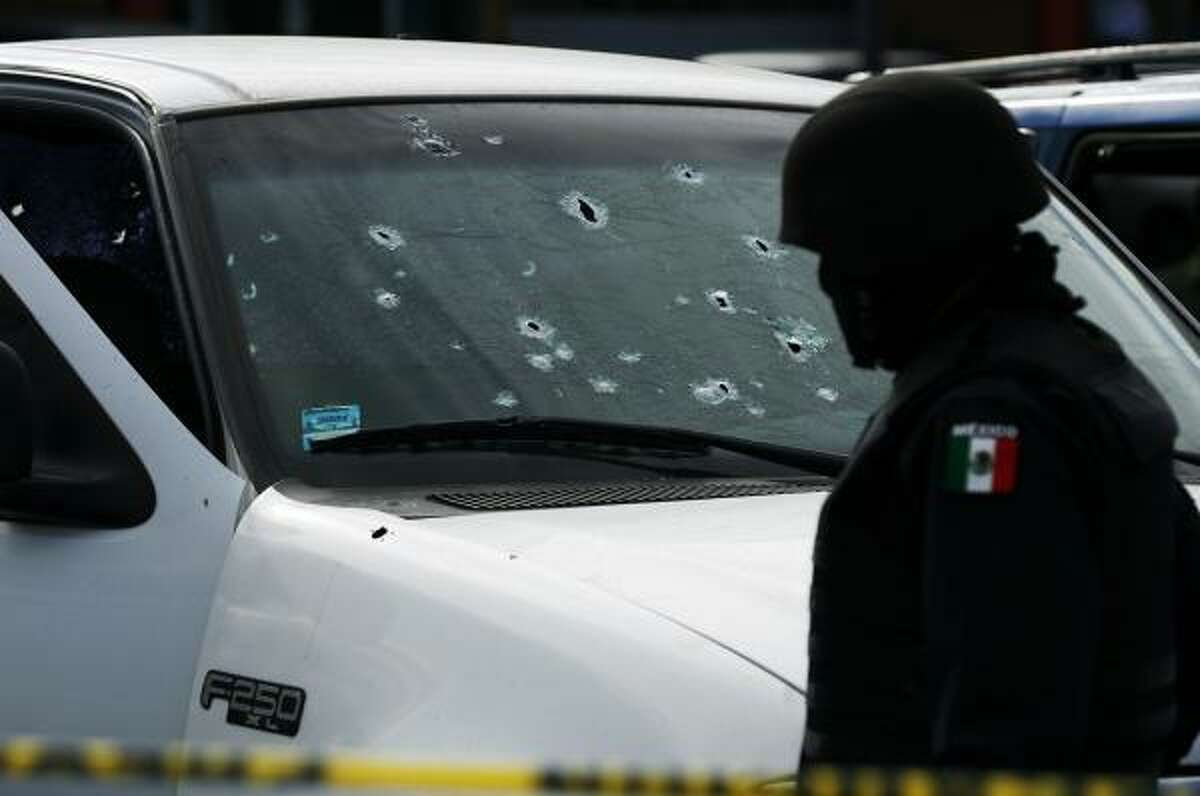 A police officer in Tijuana, Mexico, investigates the scene where a woman was killed by gunmen in a parking lot last week.