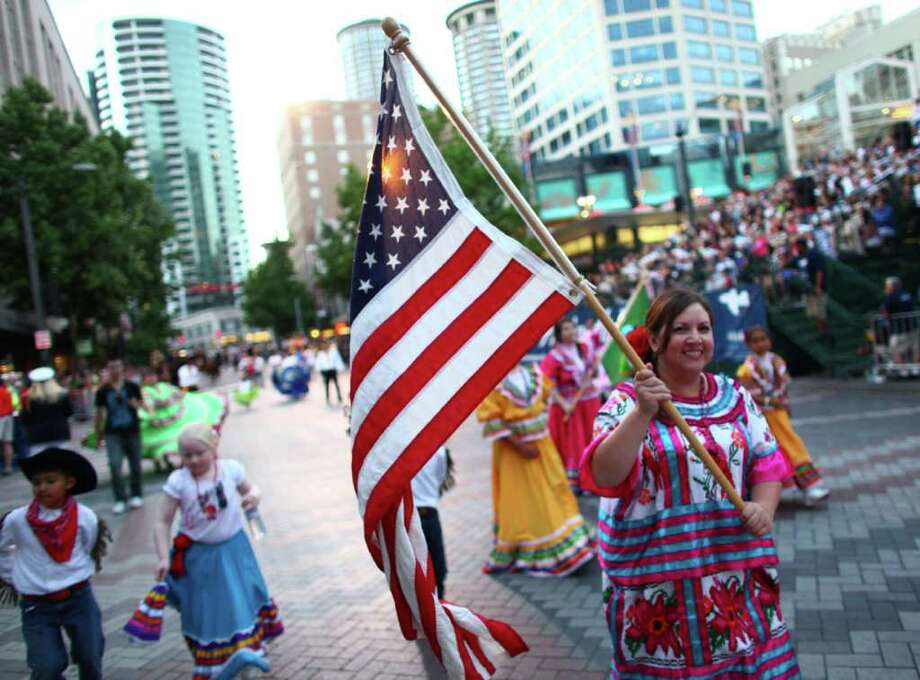 A flag is carried during the Seafair Torchlight  Parade. Photo: JOSHUA TRUJILLO / SEATTLEPI.COM