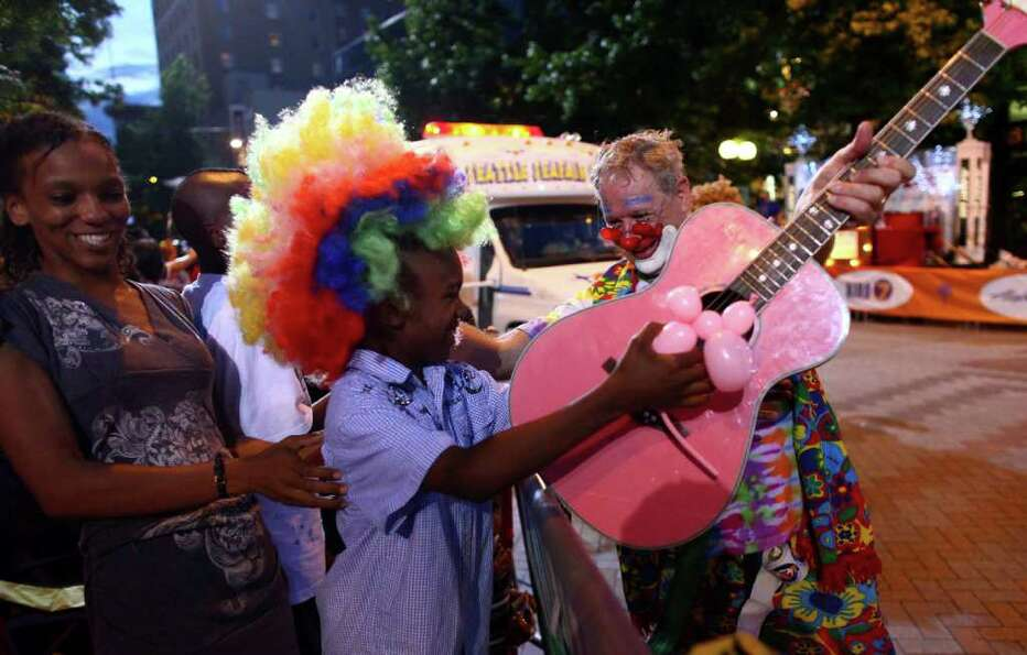 A clown hands his wig and guitar to Kevin Davis, Jr., 7, during the Seafair Torchlight  Parade.