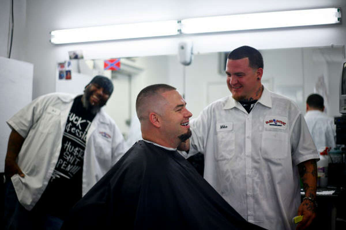 Houston rapper Paul Wall (center) gets his hair cut by Mike McCorquodale (right) while A.J. Jones (left) looks on while at Bad Boyz Barber Shop in Houston.