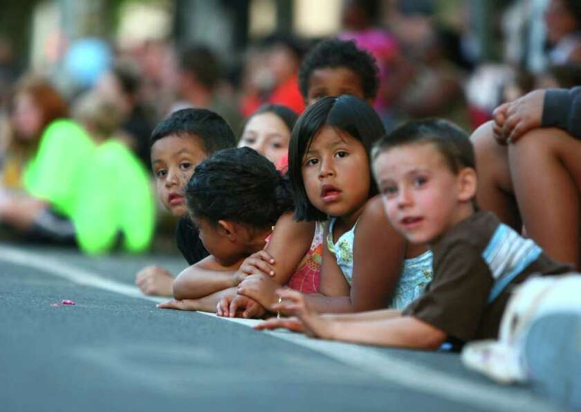 Young spectators watch the action from the street.