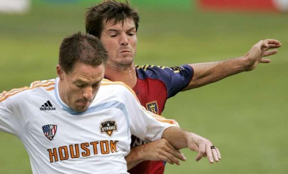 Kyle Brown, right, battles with Dynamo midfielder Richard Mulrooney during a game last season. Photo: Douglas C. Pizac, AP