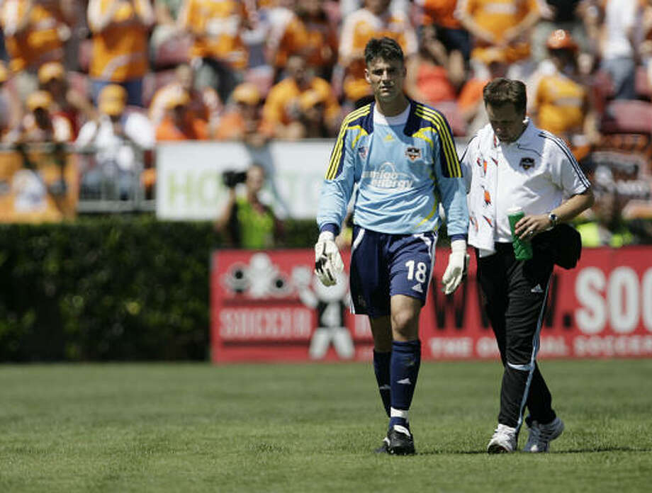 Dynamo goalkeeper Pat Onstad, left, walks off the field after a collision with an FC Dallas player on April 6 during the home opener at Robertson Stadium. Photo: Julio Cortez, Houston Chronicle