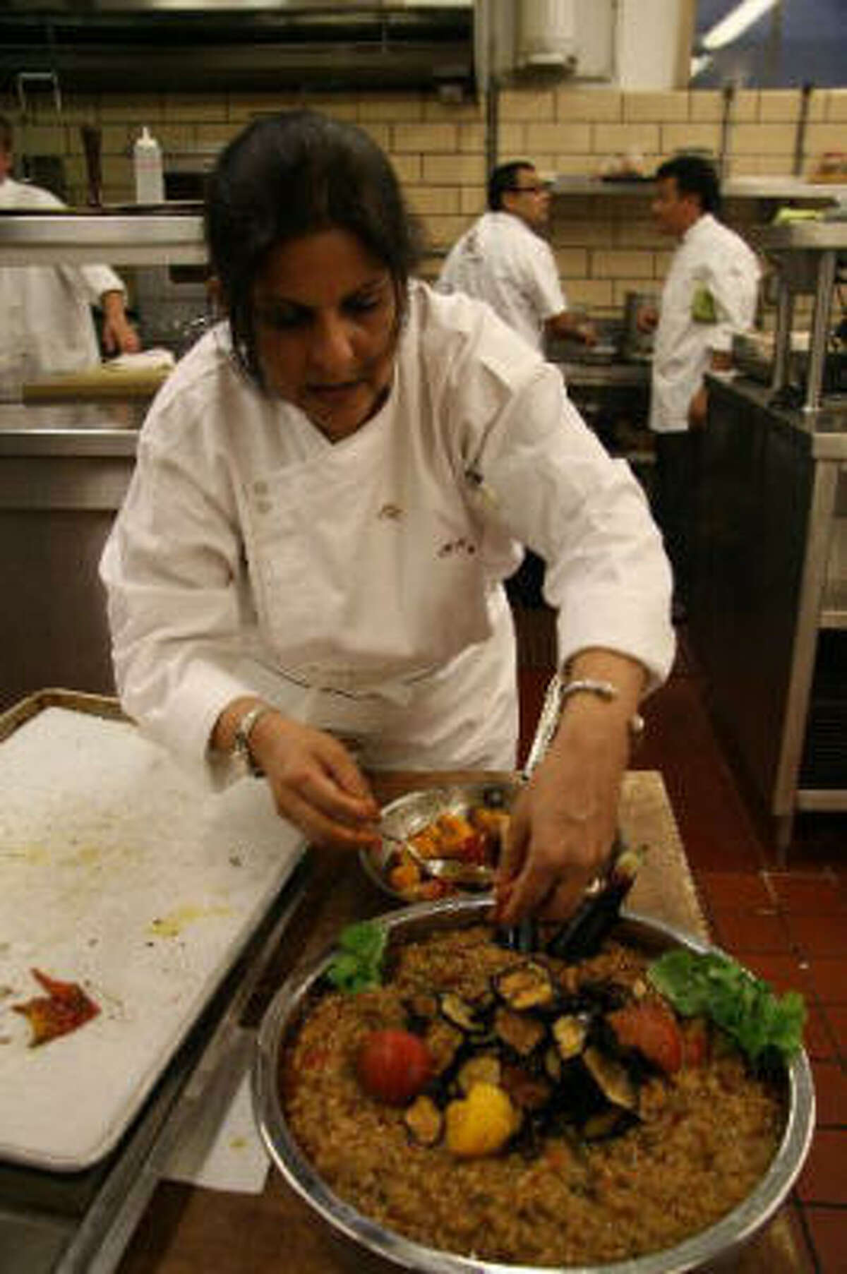 Kiran's chef-owner Kiran Verma puts the finishing touches on her eggplant appetizer before serving it at the event.