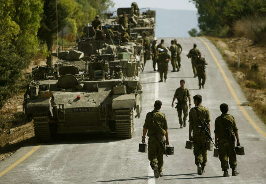 Israeli troops and tanks line up on a road near the Israeli town of Avivim near the Lebanese border today. Photo: DAVID GUTTENFELDER, AP