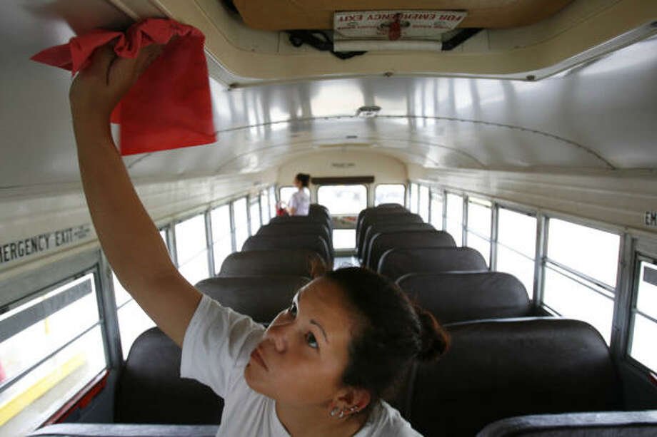 Alvin Independant School District employee Stacey Allen, 18, cleans a school bus in preparation for the upcoming school year in Alvin Tuesday. Alvin ISD says it can't afford to pick-up children who live less than two miles from their schools. In Texas, with a few exceptions, the state helps pay to bus students living two miles or farther from school. Photo: Sharon Steinmann, Houston Chronicle