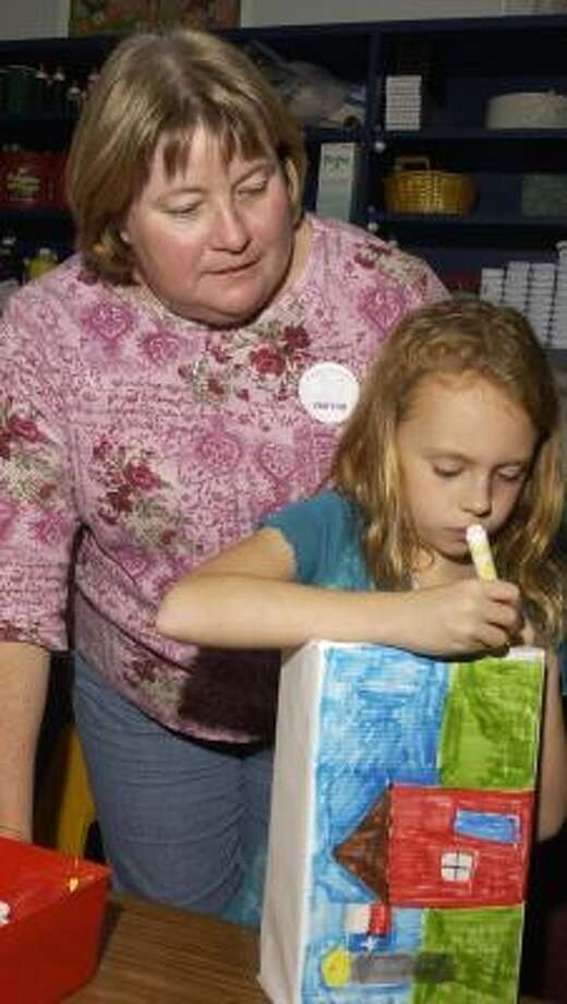 Eight-year old Kristin Trobaugh, whose dad is in the Texas National Guard, works on her gift box.  Standing with her is gift box project head Bernadette Johnson. Fielder Elementary School art classes are preparing gift boxes for U.S. soldiers in Iraq. Photo: Eddy Matchette, For The Chronicle