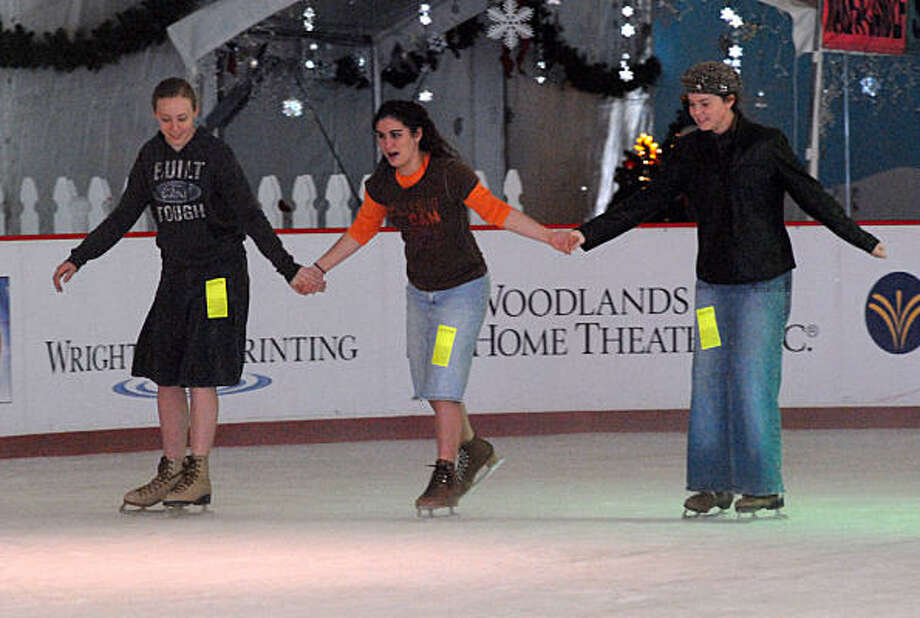 Kayla Hayden, left, Kara Bashall and Chelsea Boone hold hands and ice skate at The Ice Rink in The Woodlands. Photo: David Hopper, For The Chronicle