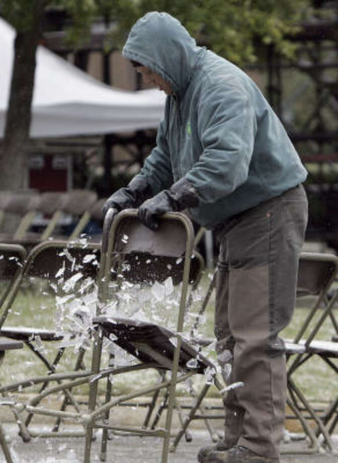 George Smith breaks ice off a chair that had been set up for Gov. Rick Perry's inauguration Tuesday. Photo: LM Otero, AP
