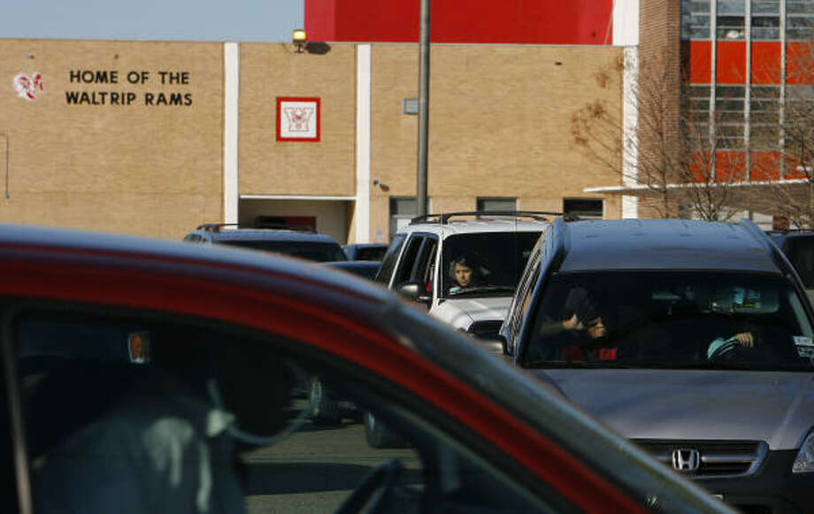 Cars line up to leave Waltrip High School on Thursday afternoon. A high percentage of teenagers surveyed nationally reported seeing their peers talking on the phone and using hand-held devices while driving. Photo: Steve Campbell, Chronicle