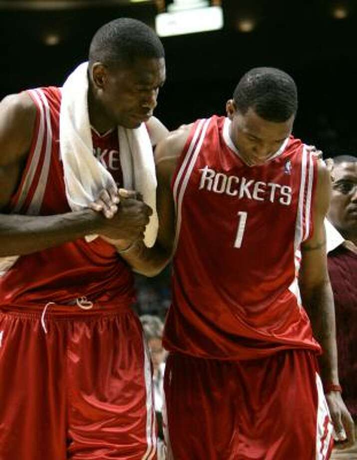 After twisting his knee late in Wednesday's 99-95 win at Portland, Tracy McGrady (1) is helped to the Rockets' bench by Dikembe Mutombo. Photo: Don Ryan, AP