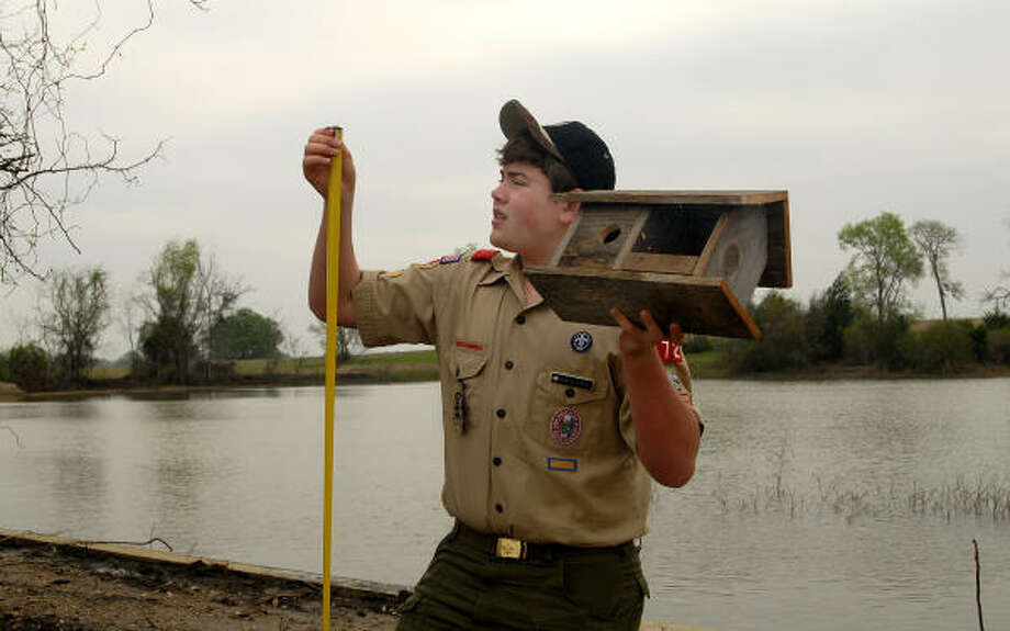 Edwin Hoff of Montgomery measures the height of a new birdhouse he has built and is placing in the new Memory Park near Charles B. Stewart West Branch Library. Edwin is working on several undertakings for the park as part of his Eagle Scout project. Photo: David Hopper, For The Chronicle
