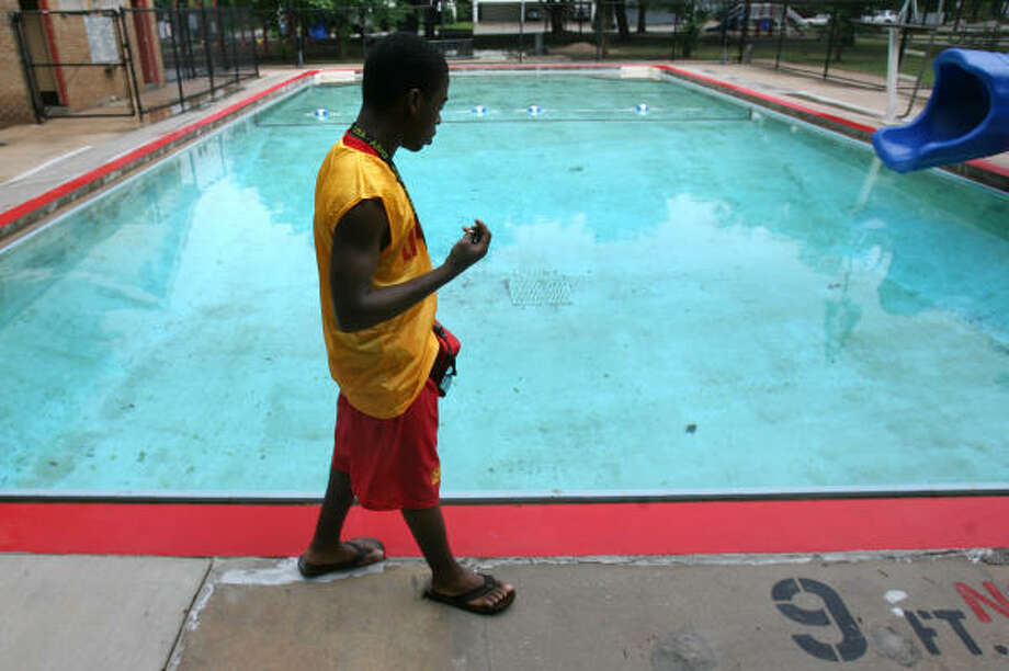 "Lifeguard Rushed Smith paces the empty pool area at Ervan Chew Park on Dunlavy on Saturday, the opening day for city pools. ""As long as it's not thundering and lightning, we stay open,'' said Hank Allen, of the city's Parks and Recreation Department. Photo: Sharon Steinmann, Chronicle"