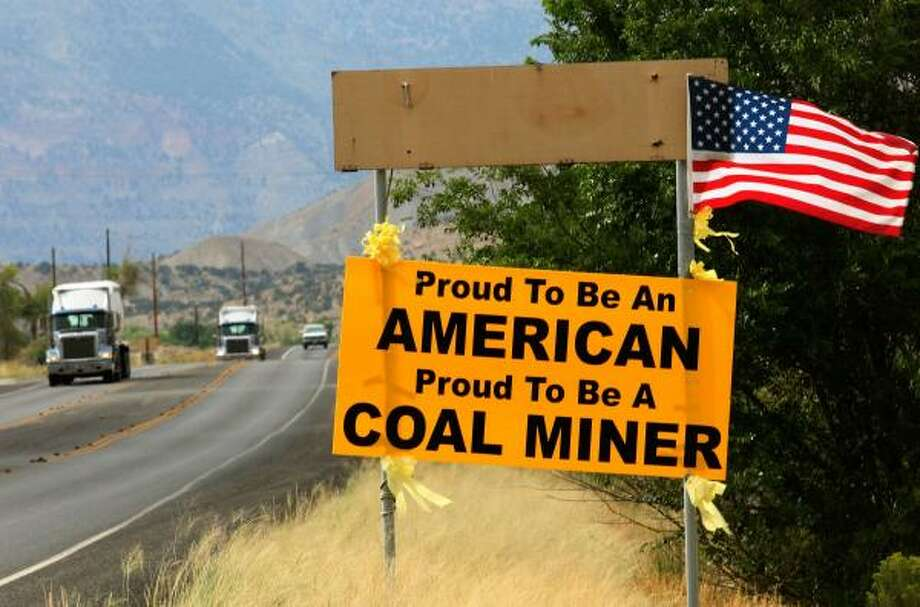 Coal trucks pass a banner near the Canyon View school where families of six coal miners await news Tuesday near Huntington, Utah. Photo: Justin Sullivan, Getty Images