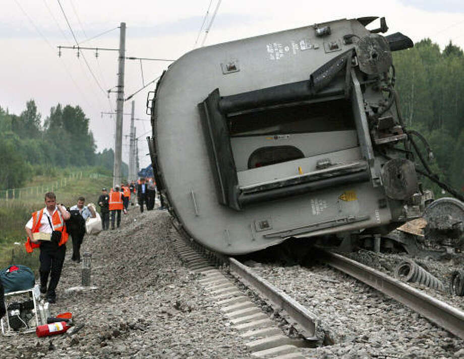 Railway workers pass the wreckage of the train near Novgorod, about 300 miles north of Moscow. Photo: YEVGENY ASMOLOV, AFP/Getty Images