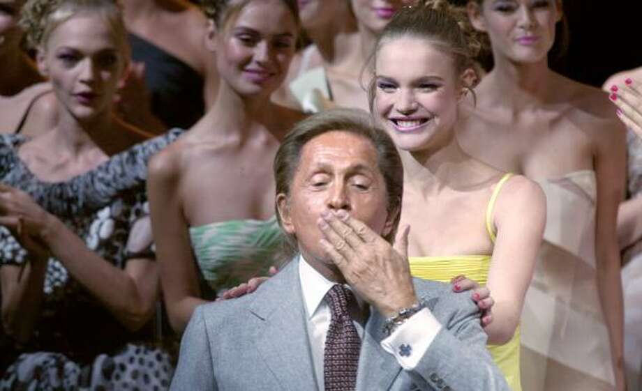 Italian designer Valentino blows a kiss to the crowd at the end of his show Wednesday in Paris. Photo: FRANCOIS GUILLOT, AFP/GETTY IMAGES