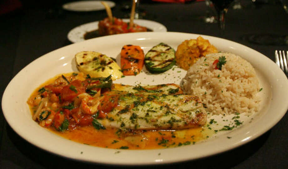 This Peruvian dish of corvina, a South American fish somewhere between sea bass and snapper in texture, is served with rice and vegetables. Photo: Mayra Beltran, Chronicle