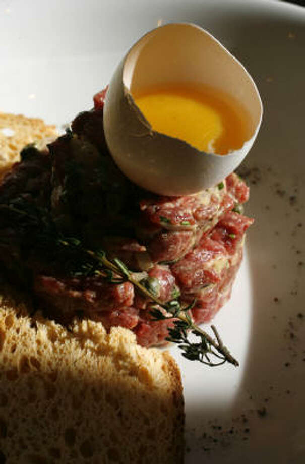 Brasserie Max & Julie's steak tartare is dramatically presented with a little egg yolk. Photo: Karen Warren, Chronicle