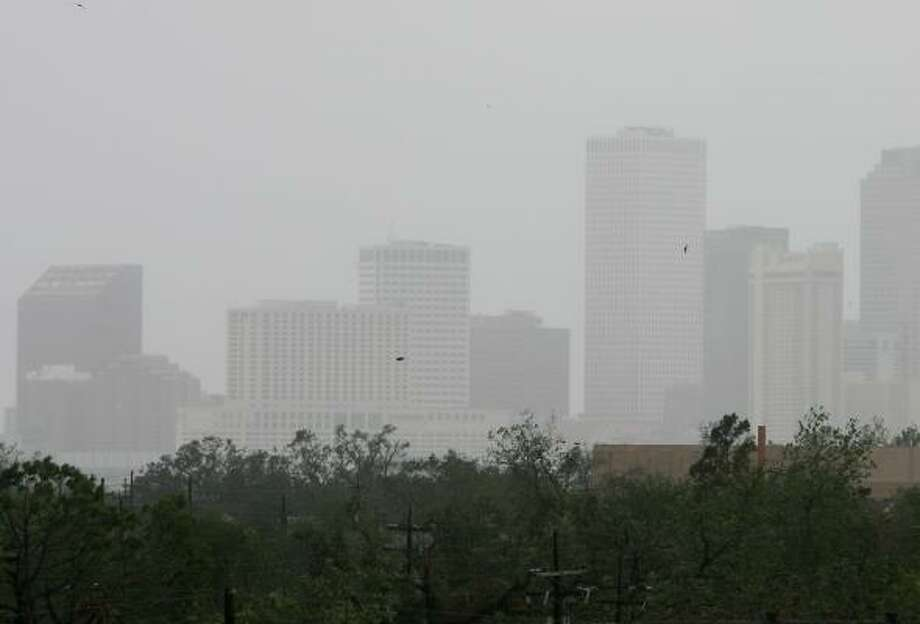 Showers from a feeder band of Hurricane Rita obscure the downtown skyline of New Orleans in September 2005. A long list of companies that formerly called New Orleans home left after Hurricane Katrina. Photo: Ethan Miller, GETTY IMAGES FILE
