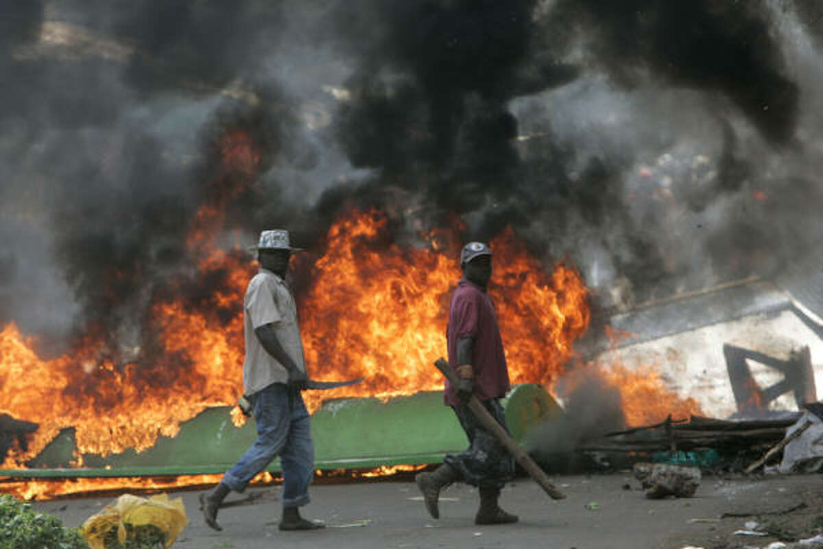 Armed with machetes, supporters of the opposition Orange Democratic Movement passes burning barricades during rioting in Nairobi's Kibera slum on Saturday.
