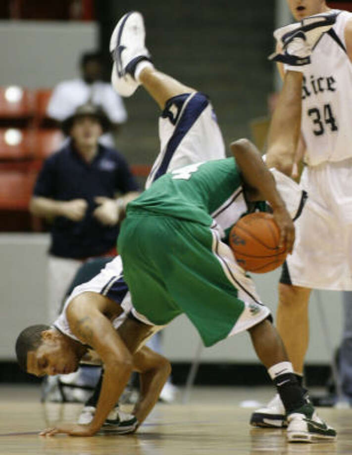 Rice's Pierre Beasley's fouls Marshall's Mark Dorris (34) during the second half of the Owls' loss. Photo: Kevin Fujii, Chronicle