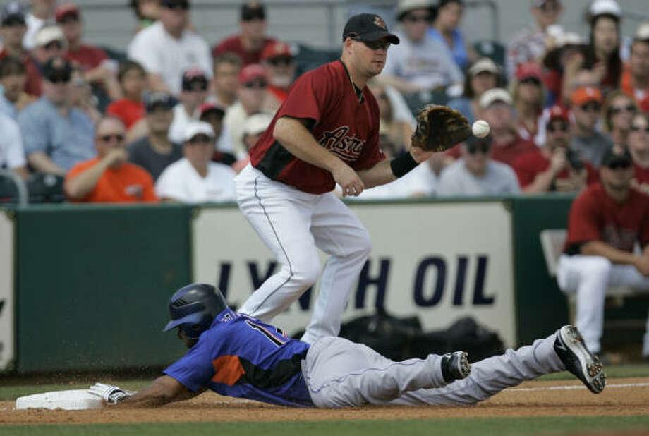 Astros third baseman Ty Wigginton, top, waits for ball as the Mets' Fernando Tatis slides safely into third base. Photo: Tony Dejak, AP
