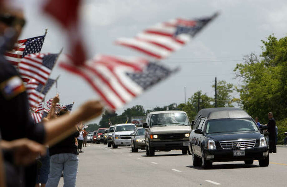 The hearse carrying 1st Lt. Timothy Cunningham, 26, passes by the hundreds of people who gathered along Highway 6 in Alvin to honor him Wednesday. Cunningham, a West Point graduate died April 23 in Golden Hills, Iraq, from injuries suffered in a vehicle incident. Photo: Johnny Hanson, Chronicle