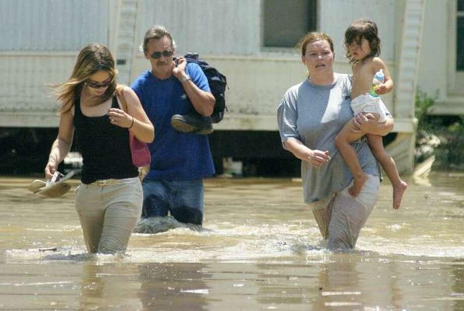 Brittney Pittman, left, John Cox, Ronda Cox and Susana Bustos, 2, retrieve belongings from their Columbus, Ind., homes Sunday. Photo: JOEL PHILIPPSEN, THE COLUMBUS REPUBLIC