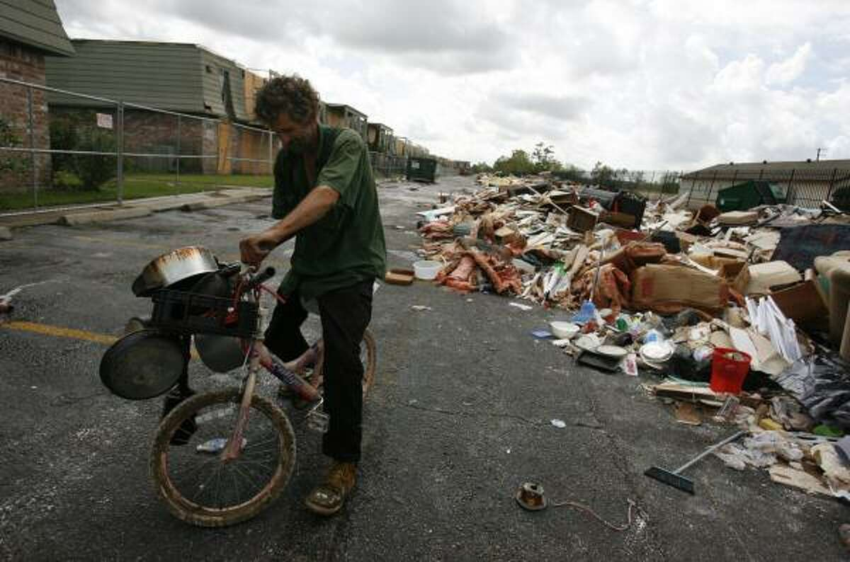 A homeless man gathers items last week from the massive trash heap growing behind Houston's Crestmont West Apartments, where at least 13 building lost their roofs in the storm.