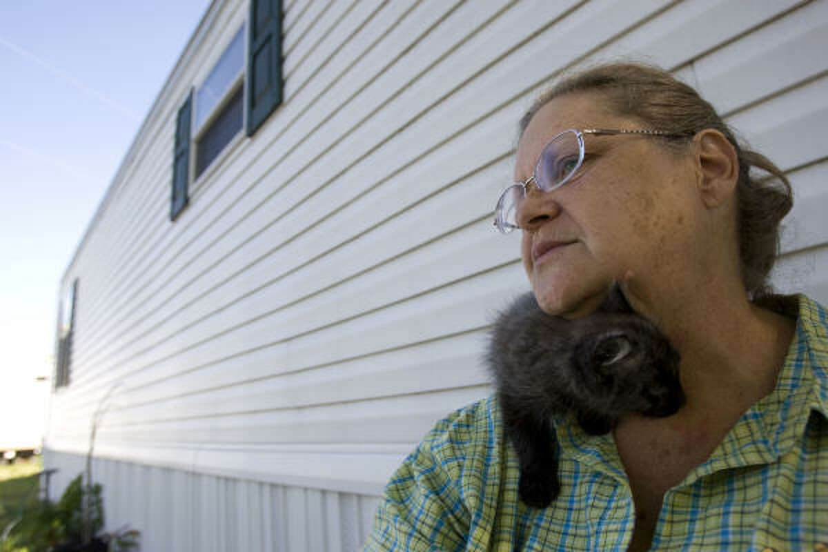 Mary Shosty and her cat Bella relax outside the FEMA mobile home she shares with her husband, L.J., in San Leon. The couple said they were happy with FEMA's response to Hurricane Ike.